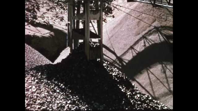 1960s: Rocks fall down chute of silo at quarry. Rocks fall off end of conveyor belt, piling up in mound. Bulldozer pulls excavator up dirt hill.