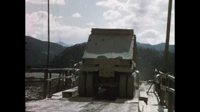 1960s: Container truck drops aggregate off and rolls away. Man closes door on elevated bridge. Conveyor belts run from concrete mill buildings.
