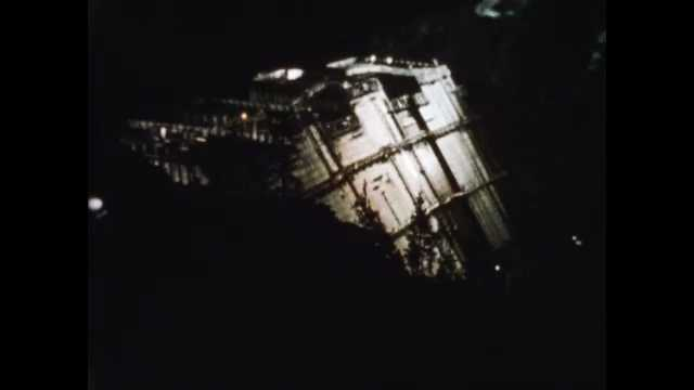 1960s: Floodlights shine on dam construction site at night. Scaffolds and walkways lead to entry hole on side of dam. Man pulls rope near inspection entryway. Dam under construction.