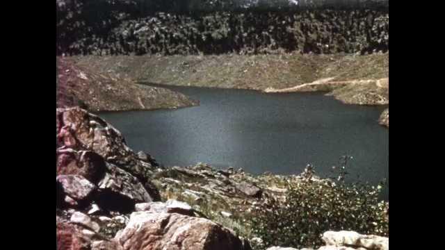 1960s: Dam sits near lake reservoir in tree-lined hills. Man drives boat across reservoir. Homes sit on shores on lake reservoir.