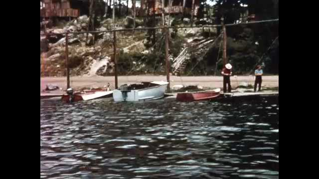 1960s: Boats and canoes line shore of lake reservoir. Sailboat floats across lake. People drive motorboat, sight-seeing boat and fishing boat on lake.