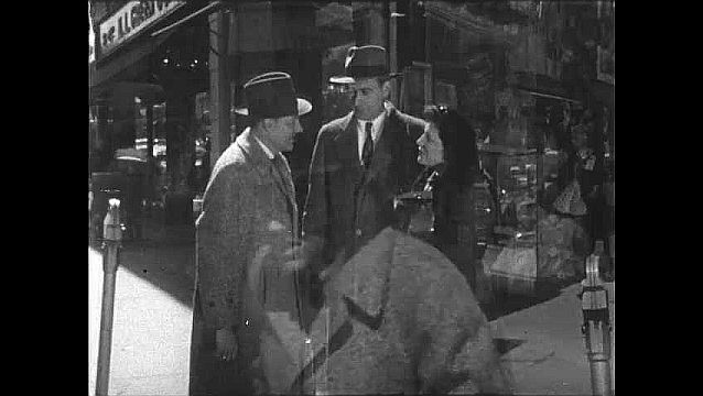 1950s: UNITED STATES: people talk in street by shops. Couple talk to man in street. Man looks at watch. Men shake hands.