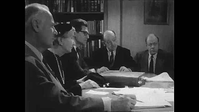 1950s: UNITED STATES: man talks to committee members in meeting. People sit in meeting. Man looks at paper.