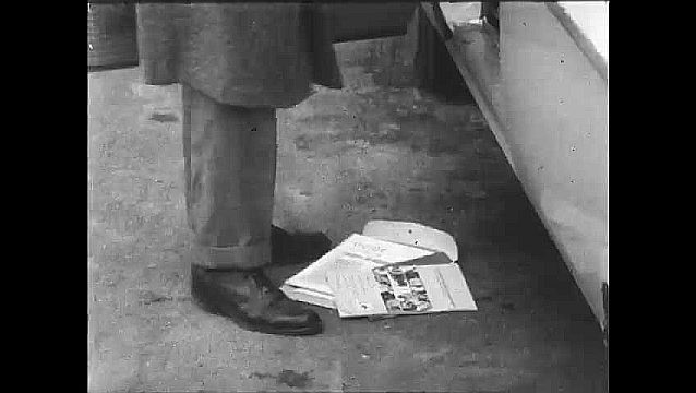 1950s: UNITED STATES: man looks at literature from floor. Man gets into car. Man reverses car. Car on road