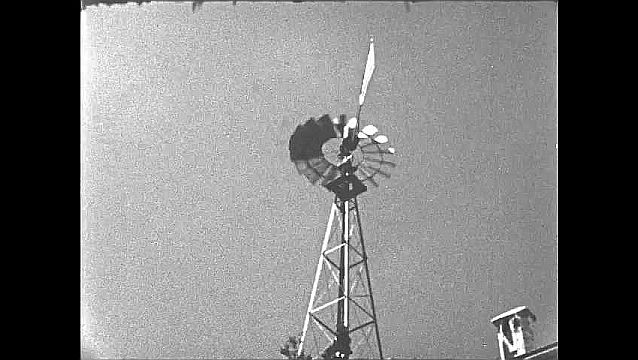 1950s: Turbine on weathervane spins.  Building.  People sit on steps and read from books.