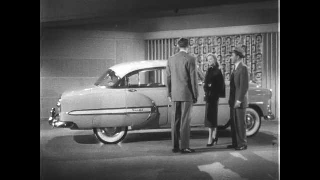 1950s: UNITED STATES: shape of Chevrolet car from side. People admire car.