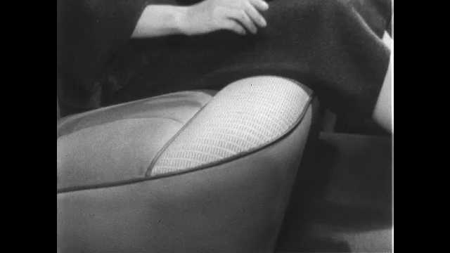 1950s: UNITED STATES: lady runs hand along upholstery of car interior