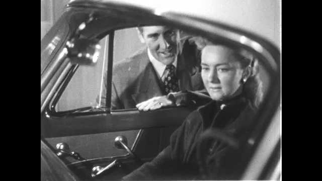 1950s: UNITED STATES: lady sits inside car. Man speaks to lady through window. Man opens door of car.