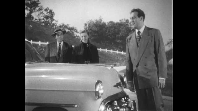 1950s: UNITED STATES: man opens bonnet on car.