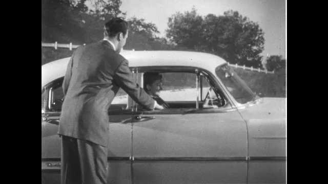 1950s: UNITED STATES: man talks to couple inside car of 1953 Chevrolet. Key start ignition switch. Dashboard of car