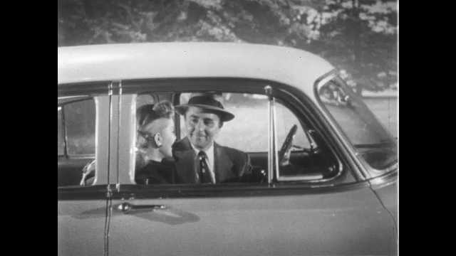 1950s: UNITED STATES: lady talks to man in car. Man stands by car.