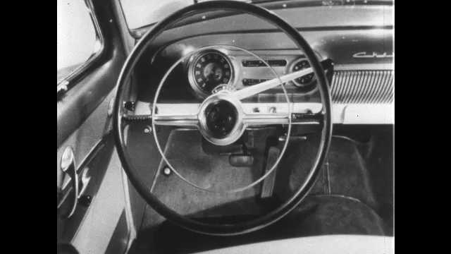 1950s: UNITED STATES: steering wheel in car. Lady talks to camera.