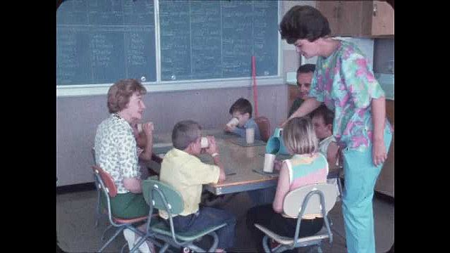 1970s: Two adults and five children sit at table in classroom. The table is laid with placemats. A woman circles the table pouring a drink into cups from a pitcher.??