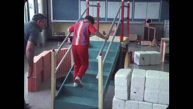 1970s:??Boy climbs the stairs holding rails as teacher watches. Another boy follows on the stairs. Boy washes hands in classroom sink. Students paint with their hands.??