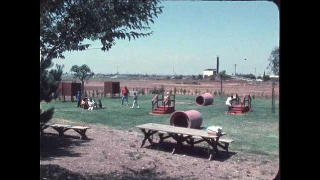 1970s:??Students and children play outside on play equipment. Students and teachers sit on ground in circle and raise their hands.??