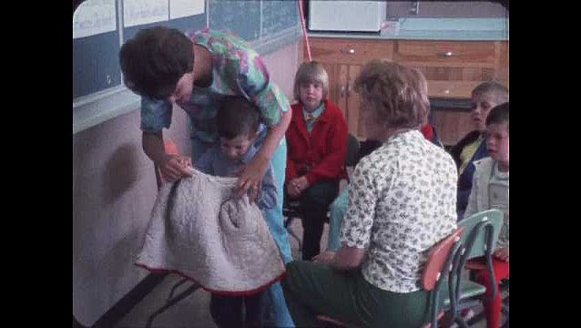 1960s: Woman helps boy hang coat on rack. Women talk to kids in classroom. Woman talks to boy, touches boy's face.