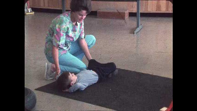 1960s: Woman helps boy roll on mat, boy crawls through tunnel. Man talks to boy climbing up play equipment.