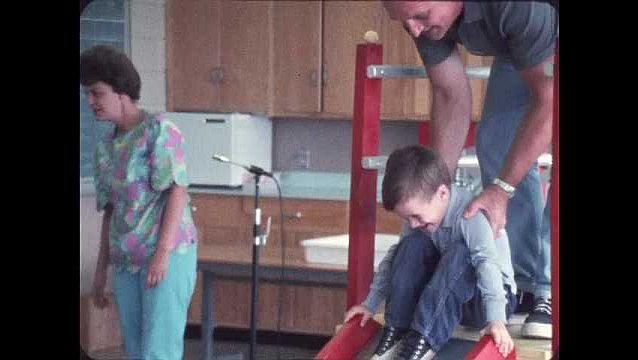 1960s: Man helps boy go down slide in classroom, women talk to kids in background. Woman playing with girl. Woman helps girl pour water. Close up, boy goes down slide.