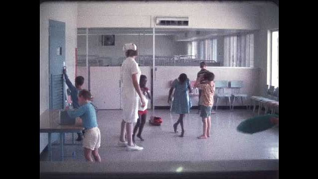 1960s: Kids playing in room with nurse.