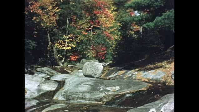 1960s: Stream flows over wide flat rocky area, man lies down, puts face in water, drinks. Man dips cup in stream, gives water to woman. Colorful fall trees. People wear backpacks, hike.