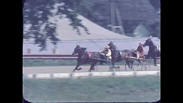 1950s: UNITED STATES: jockeys race around track with horse and trap