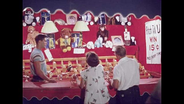 1950s: UNITED STATES: fairground at night. Fireworks at show. Couple hoop prizes on stall