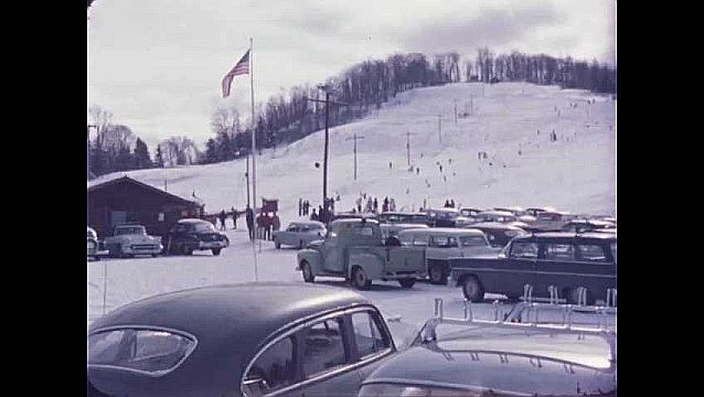 1950s: People ski down slopes on mountainside with parking lot of cars below.