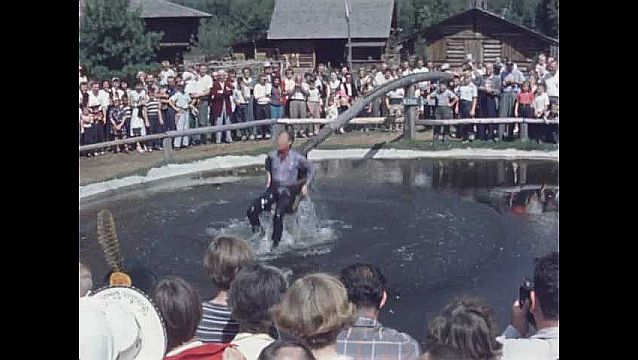 1950s: Man in cowboy clothes sits on dunking pole in water as crowd watches.
