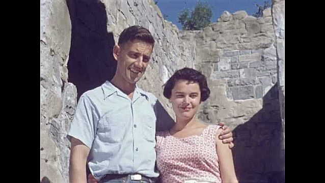 1950s: UNITED STATES: couple pose for photo by ruin