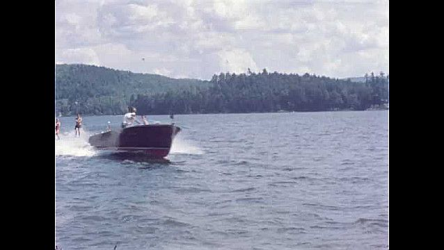 1950s: Boat.  Man and woman waterski.
