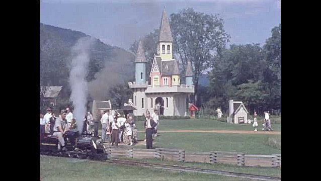 1950s: UNITED STATES: people on miniature steam train. Castle in park.
