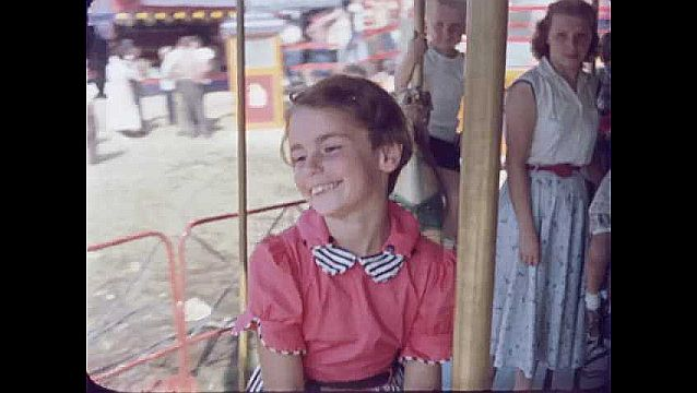 1950s: UNITED STATES: girl on fairground ride. Merry go round ride.
