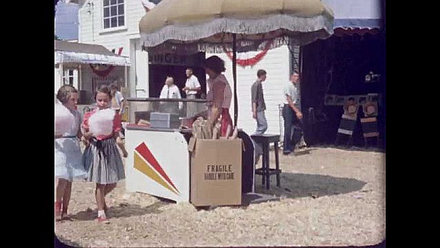 1950s: UNITED STATES: children eat cotton candy at fair.