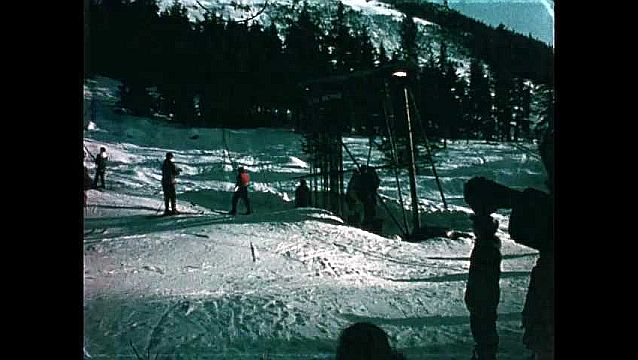 1960s: On ski slope, people grab ropes hanging from wire running up ski slope like a chairlift.
