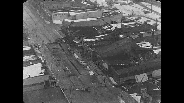1960s: Aerial view of damaged buildings, collapsed street.