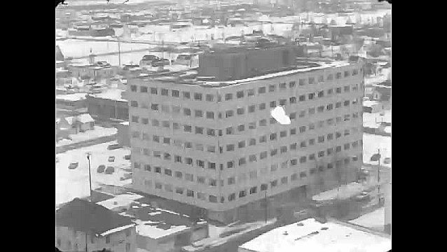 1960s: Aerial view of highrise building. View of collapsed buildings.