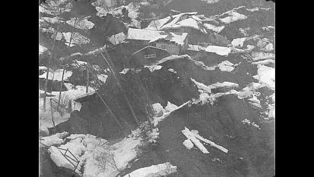 1960s: Aerial view of damaged buildings. Close ups of car under debris. Pan across damaged building. Tilt down damaged building.