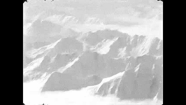 1960s: Aerial view of mountains. View of cracks in ice. Tracking shot of mountainside.