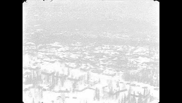 1960s: Aerial view of mountainside. Aerial view of town.