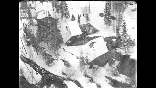 1960s: Aerial view of collapsed hillside, damaged houses. Camera in helicopter. Tilt up cracks in ground.