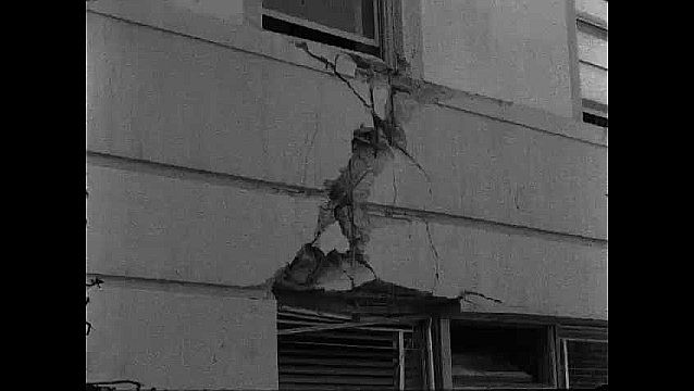 1960s: Close ups of cracks in side of building. Front of  building. Damage on building. Side of damaged building.