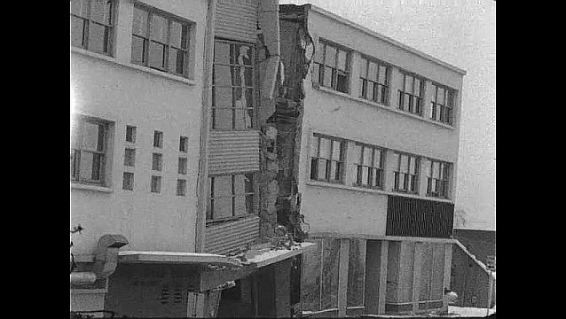 1960s: Side of damaged building. Pan across collapsed street. Cars on collapsed street. Pan across damaged building, man walking down street.