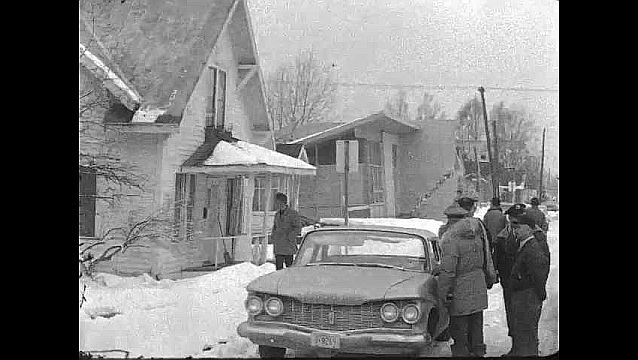 1960s: People on street, pan to damaged building. View down collapsed street. Side of damaged building. Pan across collapsed street.