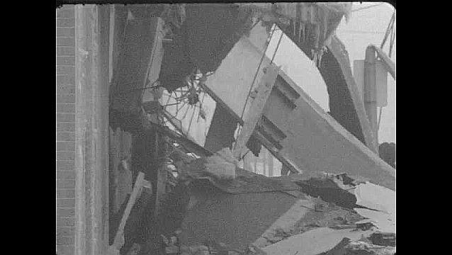1960s: ALASKA: people search through rubble. Car drives along road.