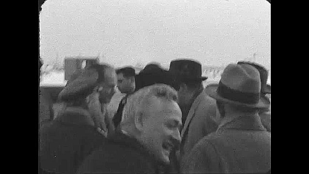 1960s: ALASKA: men at airport in winter. Men talk by plane. Man in military uniform.