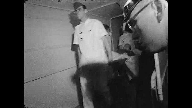 1960s: ALASKA: patient on stretcher. Evacuation of casualties by bus and plane. Transfer of patients from hospital in Anchorage