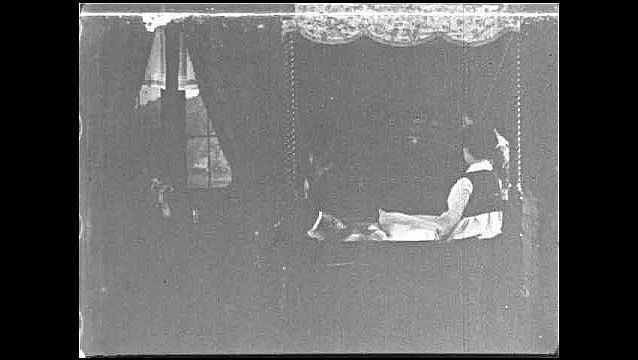 1930s: Bedroom.  Man speaks to woman in bed.  Woman and boy stand.