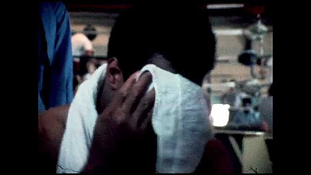 1970s: Muhammad Ali wipes face with towel, talks to women and children.