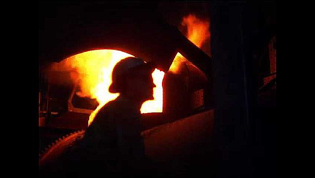 1950s: Factory.  Men work in foundry.  Molten metal pours into barrel.  Man inspects car part.