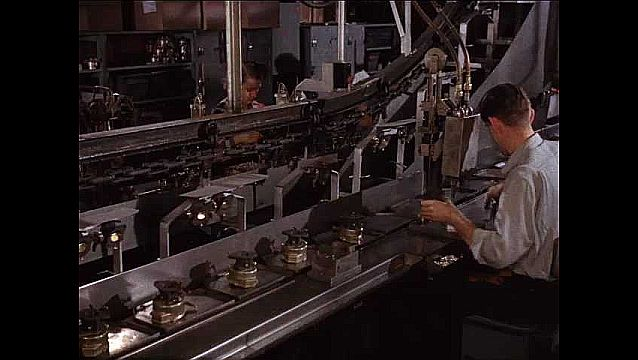 1950s: Factory.  People work on assembly line.  Machines place fittings.
